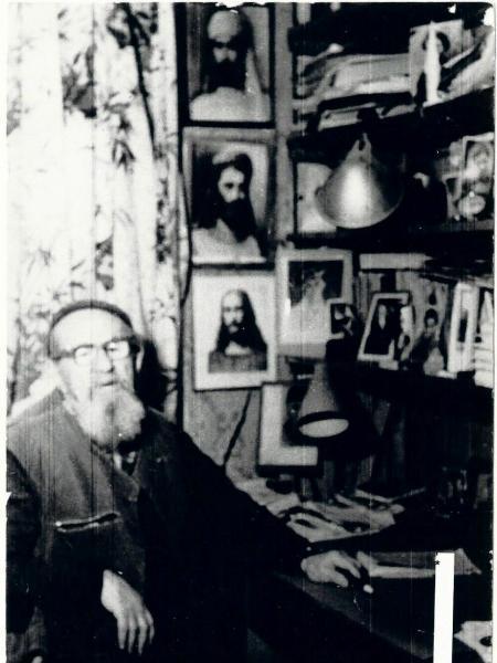 М.Ц.Спургот-Спурга у своего «иконостаса» – стеллажа, на котором было много фотографий