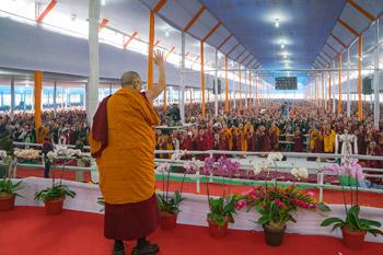 Его Святейшество Далай-лама машет рукой слушателям в начале  учений в первый день посвящения Калачакры. Фото: Тензин  Чойджор (офис ЕСДЛ)