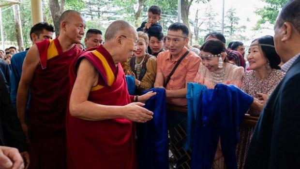 Направляясь на конференцию с российскими учеными и буддийскими учеными-философами, Его Святейшество Далай-лама приветствует верующих, собравшихся во дворе главного тибетского храма. Фото: Тензин Чойджор